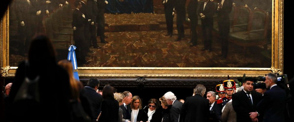In this Tuesday, July 9, 2019 photo, relatives of former Argentine President Fernando De la Rua stand beside his coffin during his wake inside Congress in Buenos Aires, Argentina. De la Rua, who attracted voters with his image as an honest statesman