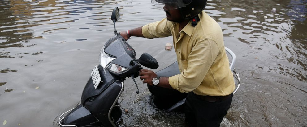 An Indian man pushes his scooter through a flooded road after heavy rainfall in Ahmadabad, India, Saturday, Aug. 10, 2019. Indias monsoon rain runs from June through September. (AP Photo/Ajit Solanki)