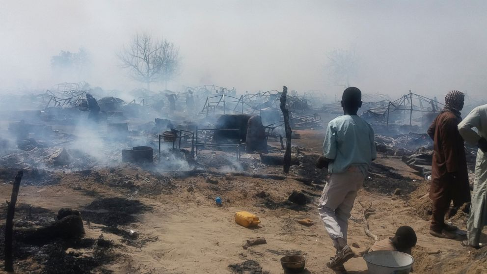 ADVANCE FOR PUBLICATION ON WEDNESDAY, FEB. 13, AND THEREAFTER - In this photo taken Thursday, Feb. 7, 2019, and provided by the International Rescue Committee (IRC), internally-displaced persons look at destroyed houses following a fire at a camp for those who had fled fighting in surrounding areas, in Monguno town, Borno State, northeastern Nigeria. Nigeria's government acknowledges an extremist resurgence by Boko Haram offshoot in the Islamic State West Africa Province, and the renewed extremist violence may threaten the validity of upcoming Saturday's election in the northeast. (Deborah Peter/International Rescue Committee via AP)