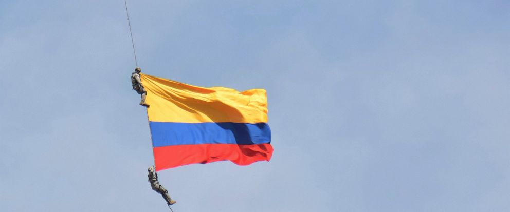 Two members of Colombia´s air force hang from a cable under a helicopter flying a Colombian flag, before plunging to their deaths when the cable snapped during the mid-air stunt at the Medellin Flower Fair in Medellin, Colombia, Sunday, Aug. 11, 2019