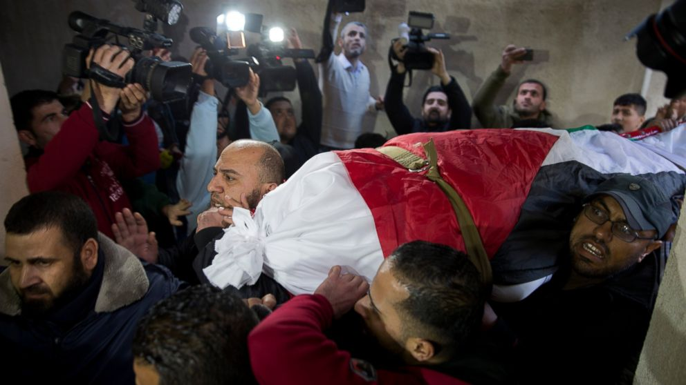 Mourners carry the body of Palestinian woman, Amal al-Taramsi, 43, who was killed by Israeli troops during Friday's protest at the Gaza Strip's border with Israel, into the family home during her funeral in Gaza City, Saturday, Jan. 12, 2019. (AP Photo/Khalil Hamra)