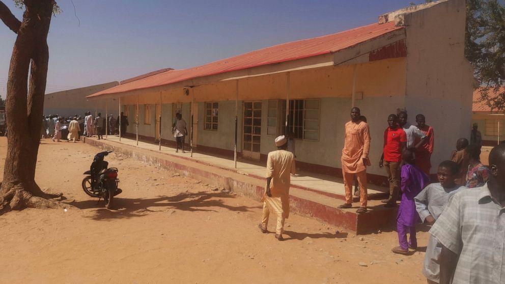 Pessoas se reúnem dentro da Escola Secundária de Ciências do Governo em Kankara, Nigéria, sábado, 12 de dezembro de 2020. A polícia nigeriana afirma que centenas de alunos estão desaparecidos depois que homens armados atacaram a escola secundária no estado de Katsina, no noroeste do país