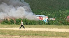 A man walks past a burning An-24 plane a fire after a crash during a landing in Nizhneangarsk, Republic of Buryatia, Russia, Thursday, June 27, 2019. According to the Russian Emergency Ministry, the two dead were members of the cabin crew. Forty-six