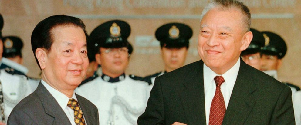 FILE - In this file photo taken Tuesday, July 1, 1997, then Hong Kongs newly inaugurated Chief Executive Tung Chee-hwa, right, receives a book bearing a picture of a statue from then Chinese Foreign Minister Qian Qichen during a ceremony in Hong Kon