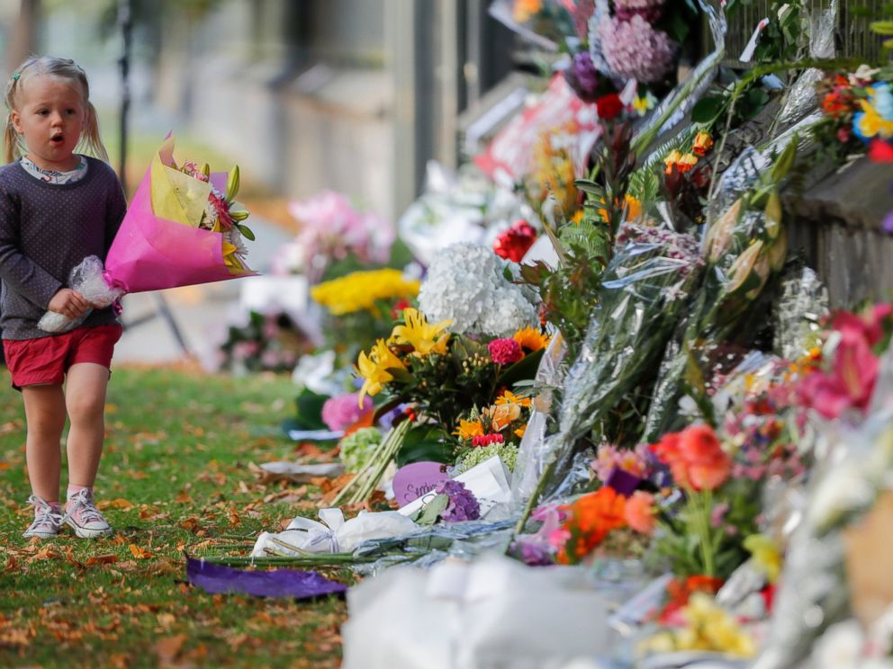 A girl walk to lay flowers on a wall at the Botanical Gardens in Christchurch, New Zealand, Sunday, March 17, 2019. New Zealands stricken residents reached out to Muslims in their neighborhoods and around the country on Saturday, in a fierce determi