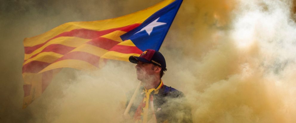 "A man holding an independence flag is seen through the smoke thrown by demonstrators during the Catalan National Day in Barcelona, Spain, Wednesday, Sept. 11, 2019. The traditional September 11, called ""Diada"", marks the fall of the Catalan capital t"