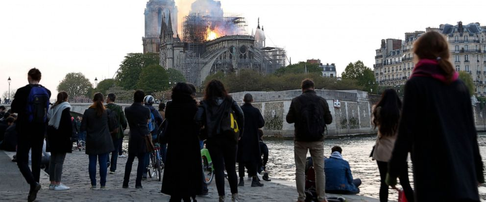 People standing on the banks of the river Seine watch as flames and smoke rise from Notre Dame cathedral as it burns in Paris, Monday, April 15, 2019. Massive plumes of yellow brown smoke is filling the air above Notre Dame Cathedral and ash is falli
