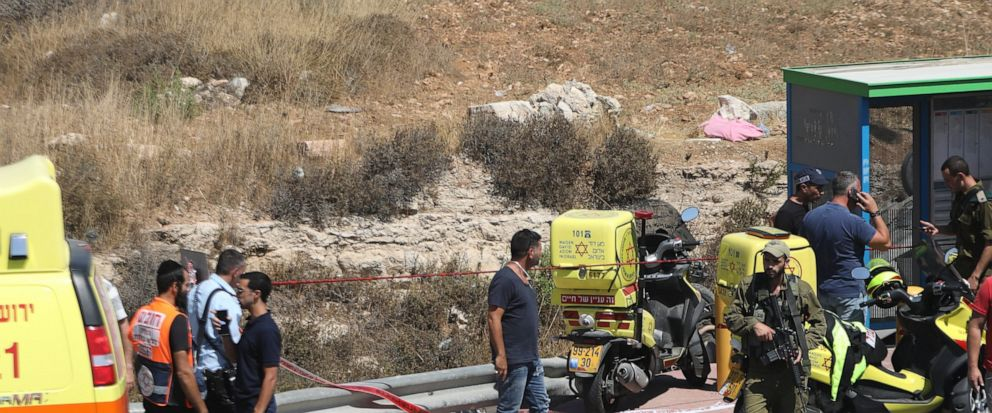 Israeli security and emergency services stand at the scene of an car ramming attack near Gush Etzion settlement cluster in the West Bank, Friday, Aug. 17, 2019. The Israeli military says a Palestinian driver has been shot and killed after he rammed h