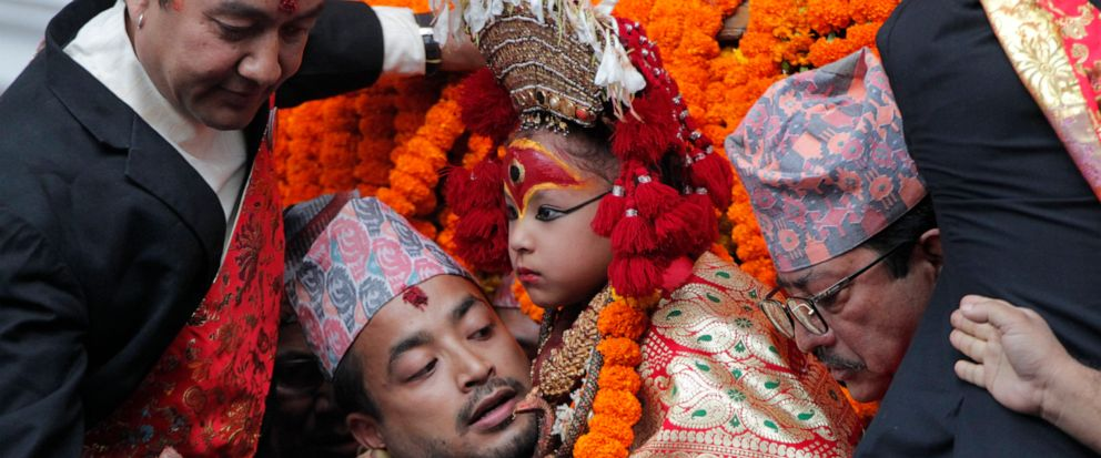 A devotee carries a revered living goddess Kumari, center, to a chariot during Indra Jatra festival, an eight-day festival that honors Indra, the Hindu god of rain, in Kathmandu, Nepal, Friday, Sept. 13, 2019. The living goddess was pulled around the