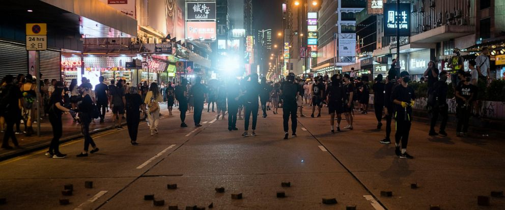 Riot police chase protesters near a demonstration in Hong Kong, Monday, Oct. 7, 2019. Tens of thousands of masked protesters marched defiantly in the city center Sunday, but the peaceful rallies quickly degenerated into chaos at several locations as