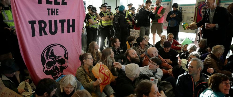 Police Officers stand guard as Extinction Rebellion demonstrators peacefully block an entrance at City Airport in London, Thursday, Oct. 10, 2019. Some hundreds of climate change activists are in London during a fourth day of world protests by the Ex