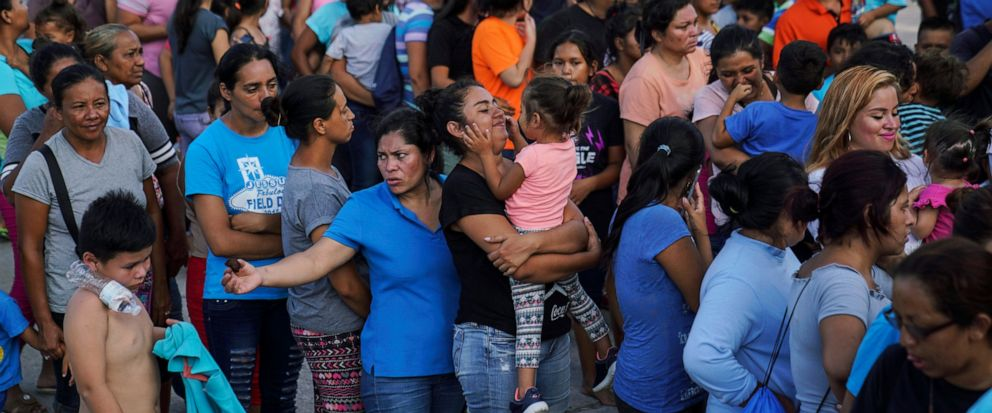 "In this Aug. 30, 2019, photo, migrants, many who were returned to Mexico under the Trump administration's ""Remain in Mexico,"" program wait in line to get a meal in an encampment near the Gateway International Bridge in Matamoros. Many shelters at the"
