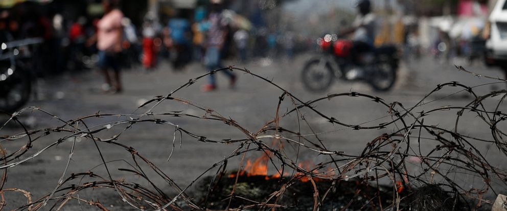 People walk and drive motorcycles past a barricade of barbed wire and the remains of burning tires, set up by anti-government protesters who are trying to paralyze transport and commerce to pressure President Jovenel Moise to resign, in Port-au-Princ