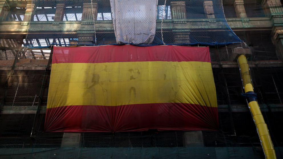 A huge Spanish flag hangs from a building under construction in downtown Madrid, Spain, Friday, Feb. 15, 2019. The prime minister of Spain has called early general elections for late April, the third such ballot in less than four years in an increasingly fragmented partisan landscape and with Catalonia's independence push dominating the political debate. (AP Photo/Andrea Comas)