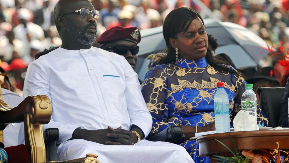 """FILE - In this Jan. 22, 2018, file photo, Liberia's new President George Weah, left and his wife, Clar Weah, right, sit during his inauguration ceremony in Monrovia Liberia. Star footballer-turned-politician George Weah marks a year as Liberia's president on Tuesday Jan. 22, 2019, as many in the impoverished country debate whether he has begun to deliver on dramatic campaign promises. FIFA's 1995 player of the year in his inaugural speech vowed to give the West African nation's young population hope through job creation and a war on corruption, saying """"Liberians will no longer be spectators in their own economy."""" (AP Photo/Abbas Dulleh, File)"""