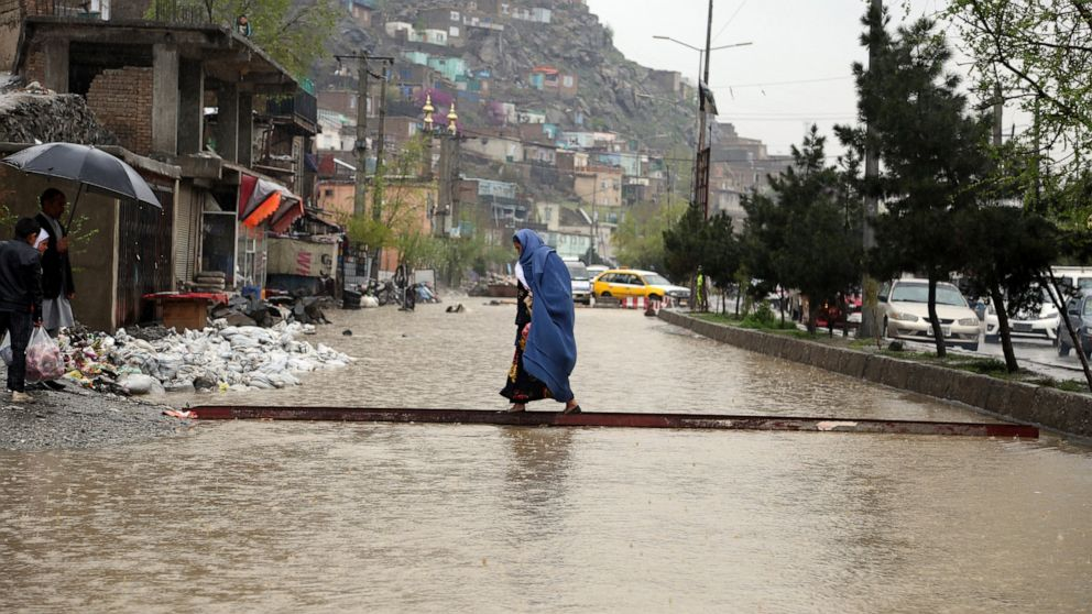 An Afghan woman walks through flood water as heavy rain falls in Kabul, Afghanistan, Tuesday, April 16, 2019. Afghan officials say at least five more people have been killed and 17 are missing as a new wave of heavy rains and flooding swept across the country's western Herat province. (AP Photo/Rahmat Gul)