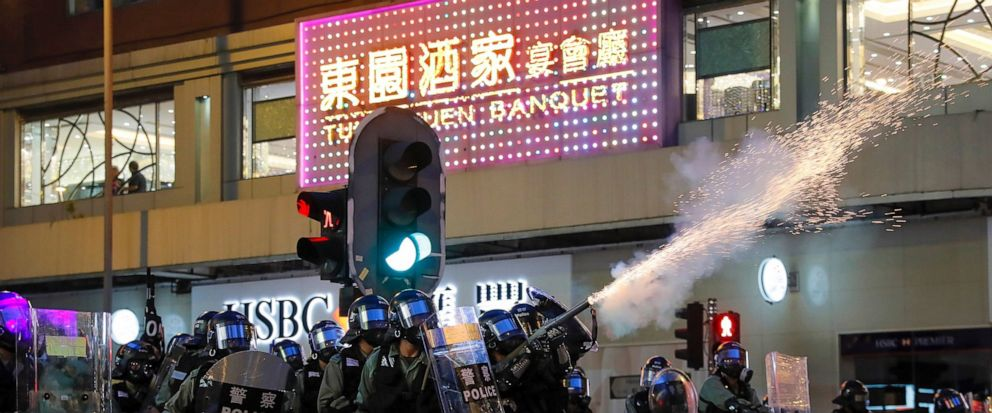 Riot police fire tear gas during the anti-extradition bill protest in Hong Kong, Sunday, Aug. 11, 2019. Police fired tear gas late Sunday afternoon to try to disperse a demonstration in Hong Kong as protesters took over streets in two parts of the As