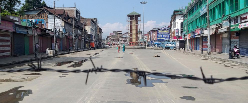 FILE- In this Thursday, Aug. 8, 2019 file photo, Kashmiri women walk at a deserted Lal Chowk square, a frequent site for anti-India protests, in Srinagar, Indian controlled Kashmir. Life is very different in the Kashmir Valley these days, under an un