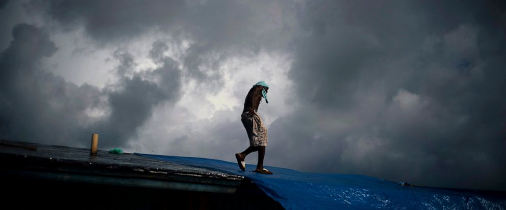 """Trevon Laing walks the roof of his house to repair the damage made by Hurricane Dorian, in Gold Rock Creek, Grand Bahama, Bahamas, Thursday Sept. 12, 2019. Trevor says """"After the hurricane they had me for dead, My momma was crying."""" When he returned,"""