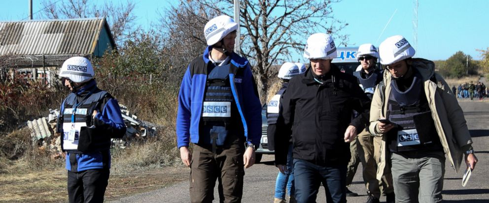 Deputy Head of the OSCE Special Monitoring Mission, Mark Etherington, second right, and other members of OSCE walk through a street near a frontline in Petrovske, Ukraine, Wednesday, Oct. 9, 2019. At least one Ukrainian police officer has been injure
