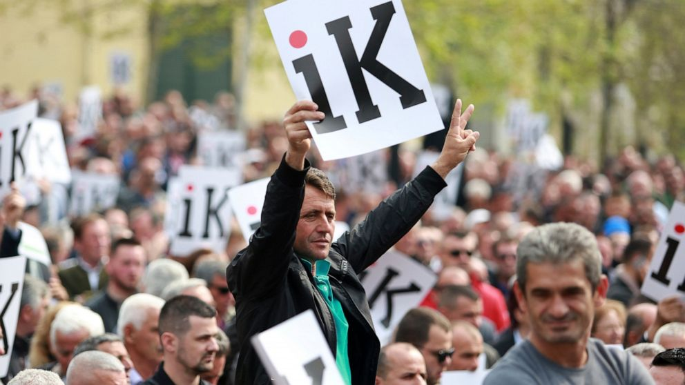 """Albanian opposition supporters hold placards that read """"Go"""" in front of the parliament building during a rally in Tirana, Wednesday, April 3, 2019. The opposition accuses the leftist Socialist Party government of Prime Minister Edi Rama of being corrupt and linked to organized crime, which the government denies. (AP Photo/Hektor Pustina)"""