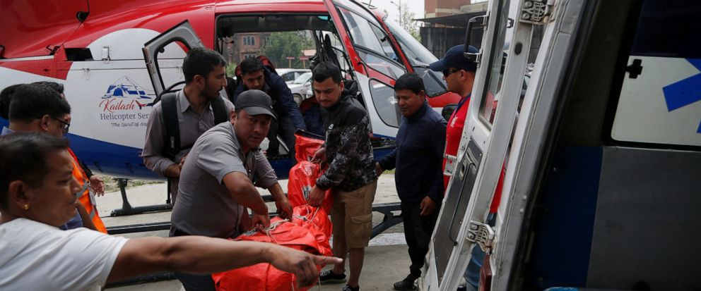 Hospital officials unload the dead body of a plane crash victim outside the Teaching Hospital in Kathmandu, Nepal, Sunday, April 14, 2019. At least three people were killed and four injured on Sunday after a small plane crashed into a parked helicopt