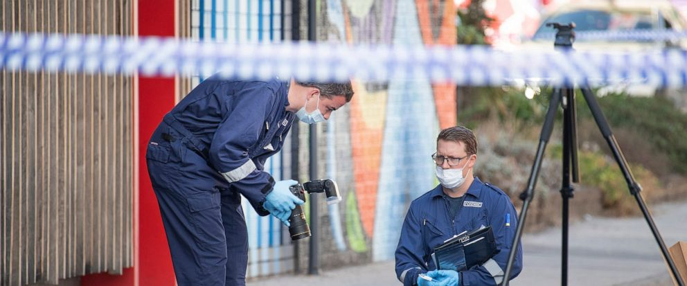 Forensic police examine items at the scene of a multiple shooting outside Love Machine nightclub in Melbourne, Sunday, April 14, 2019. A shooting outside the nightclub early Sunday left at least two people critically wounded, police said. (Ellen Smit