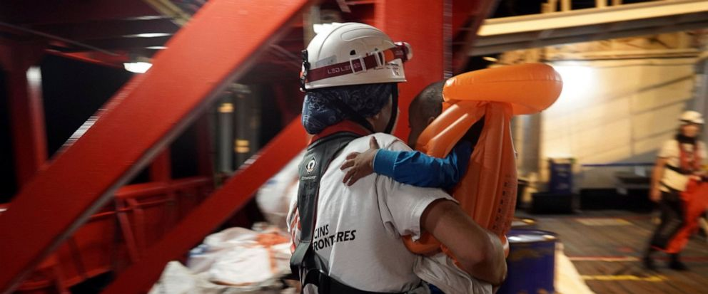 A toddler who was rescued at sea by a 14-meter sailboat Josefa, run by the group Resqship, is carried by a medic after being transferred onto the humanitarian ship Ocean Viking, in the Mediterranean Sea, late Monday, Sept. 9, 2019. Thirty-four migran