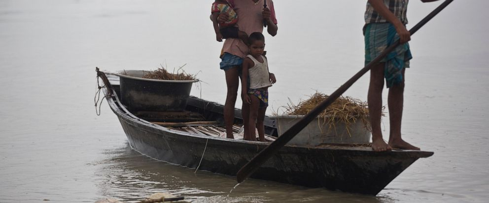 Flood effected villagers travel on a boat in Katahguri village along the river Brahmaputra, east of Gauhati, India, Sunday, July 14, 2019. Officials in northeastern India said more than a dozen people were killed and over a million affected by floodi