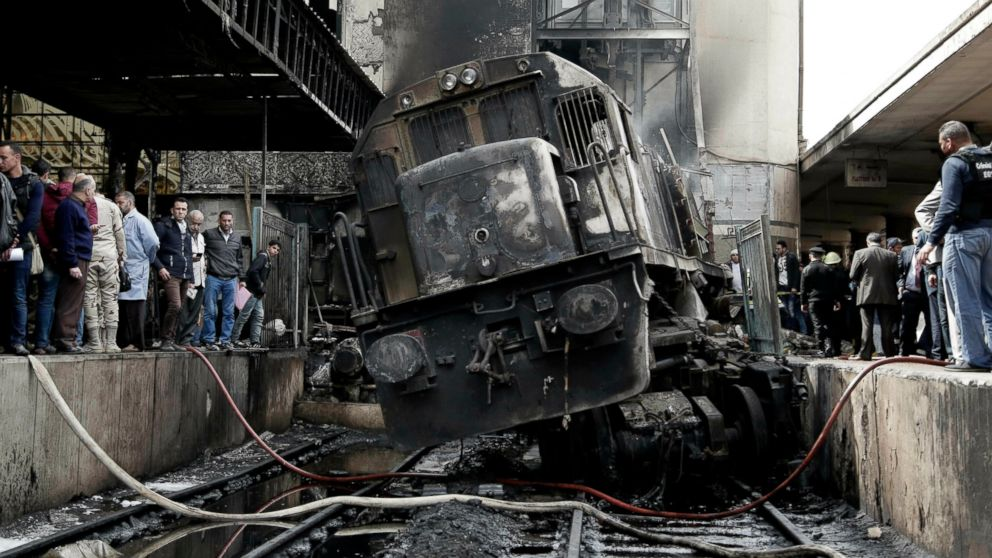 FILE - In this Wednesday, Feb. 27, 2019 file photo, people look at a damaged train inside Ramsis train station in Cairo, Egypt, Wednesday, Feb. 27, 2019. Egypt's president is appointing a military officer to lead the country's transportation ministry, less than two weeks after its minister resigned over a deadly February train crash in Cairo that killed 25 people. The general turned president, Abdel-Fattah el-Sissi, said on Sunday that Maj. Gen. Kamal el-Waziri, who heads the military's engineering authority, is awaiting approval from parliament as transportation minister. (AP Photo/Nariman El-Mofty, File)