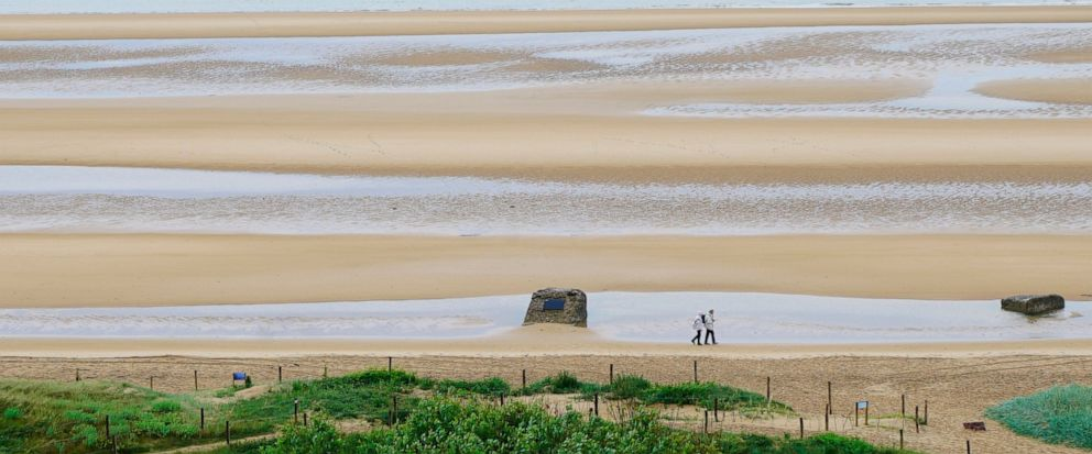 """Seen from an old German guard post, a chunk of concrete left over by German defenders sticks out on an otherwise open Omaha Beach in Colleville-sur-Mer, France, on Saturday, June 8, 2019. It is now known as """"Rays Rock,"""" because Army medic Ray Lamber"""