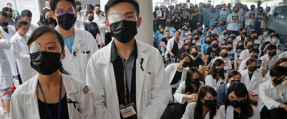 Medical staff wearing eyepatch and face masks take part in a protest against police brutality on the protesters, at a hospital in Hong Kong, Tuesday, Aug. 13, 2019. Demonstrators have in recent days focused on their demand for an independent inquiry