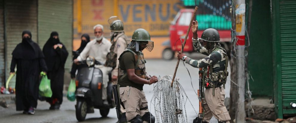 Indian paramilitary soldiers prepare to close off a street with barbwire in Srinagar, Indian controlled Kashmir, Saturday, Aug. 10, 2019. Authorities enforcing a strict curfew in Indian-administered Kashmir will bring in trucks of essential supplies