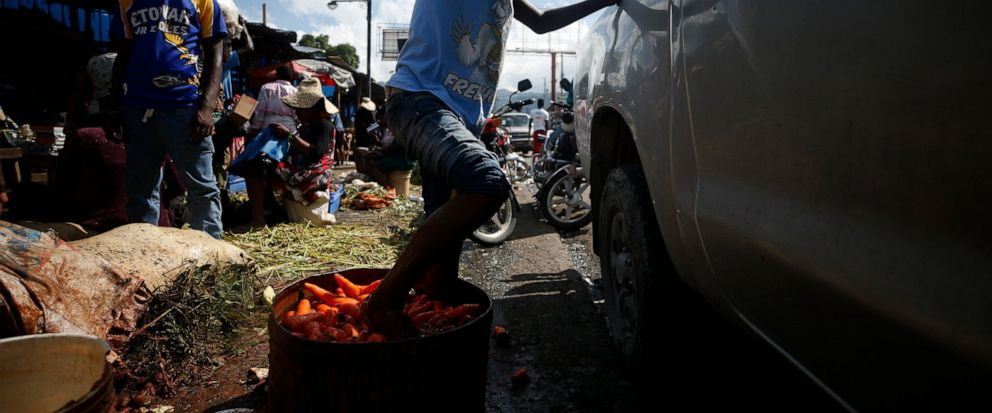 A youth cleans carrots by agitating them with his feet in a tub of murky water, at a market in Petionville, Port-au-Prince, Haiti, Wednesday, Oct. 2, 2019. There was a relative pause Wednesday in disturbances that have wracked Haitis capital for wee