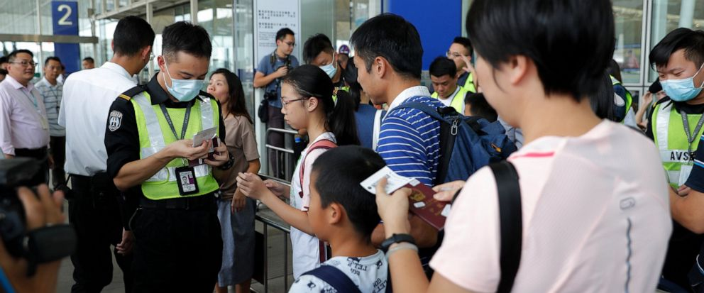 Airport security officers check on travelers flights information at the airport main entrance gate in Hong Kong, Wednesday, Aug. 14, 2019. Flights resumed at Hong Kongs airport Wednesday morning after two days of disruptions marked by outbursts of