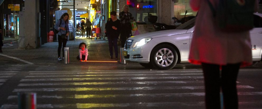 In this Wednesday, March 13, 2019 photo, an Israeli child plays with an embedded LED stoplight at a crosswalk in Tel Aviv, Israel. Tel Aviv has taken its first steps to assist pedestrians distracted by their smartphones by embedding LED stoplights at