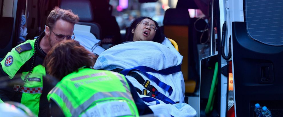 A women is taken by ambulance from Hotel CBD at the corner of King and York Street in Sydney, Australia Tuesday, Aug. 13, 2019. Police and witnesses say a young man yelling about religion and armed with a knife has attempted to stab several people in
