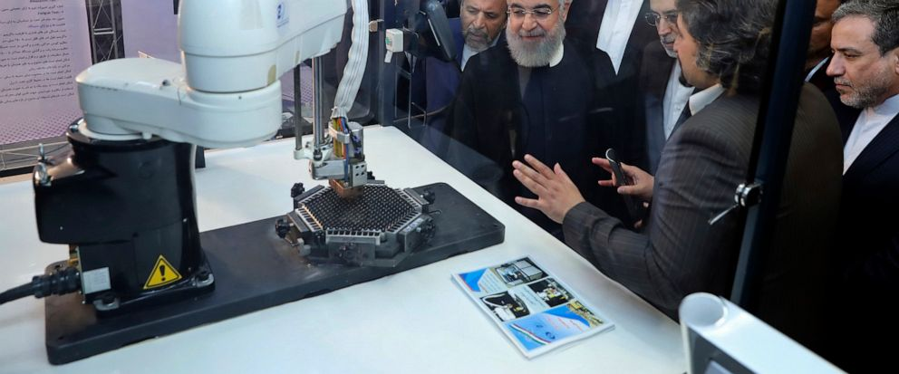 """FILE - In this April 9, 2018, file photo, released by an official website of the office of the Iranian Presidency, President Hassan Rouhani listens to explanations on new nuclear achievements at a ceremony to mark """"National Nuclear Day,"""" in Tehran, I"""