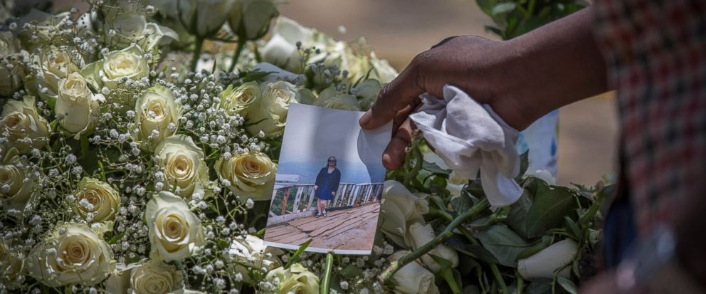 A family member puts a photo on flowers at the scene where the Ethiopian Airlines Boeing 737 Max 8 plane crashed shortly after takeoff on Sunday killing all 157 on board, near Bishoftu, south of Addis Ababa, in Ethiopia Wednesday, March 13, 2019. The