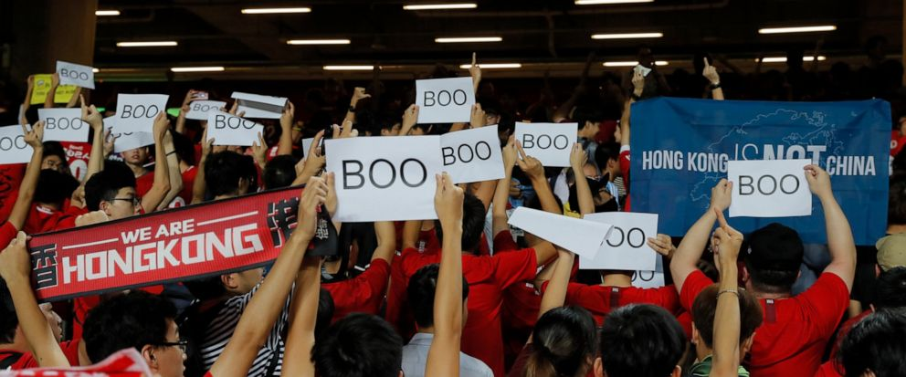 """Hong Kong soccer fans turn their back and boo the Chinese national anthem as they chant """"Hong Kong is not China"""" during the FIFA World Cup Qatar 2022 and AFC Asian Cup 2023 Preliminary Joint Qualification Round 2 soccer match between Hong Kong and Ir"""