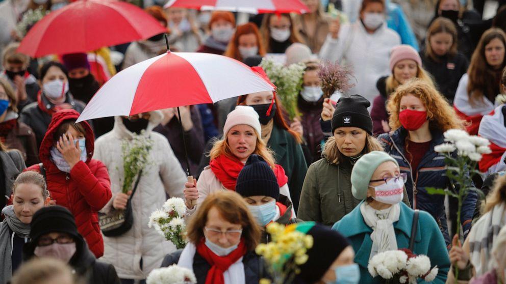 Weißrussische Frauen mit Regenschirmen in den Farben der alten belarussischen Nationalflagge nehmen an einer Kundgebung der Opposition teil, um gegen die offiziellen Ergebnisse der Präsidentschaftswahlen in Minsk, Weißrussland, am Samstag, 24. Oktober 2020, zu protestieren. Mehrere hundert Frauen sind un marschiert