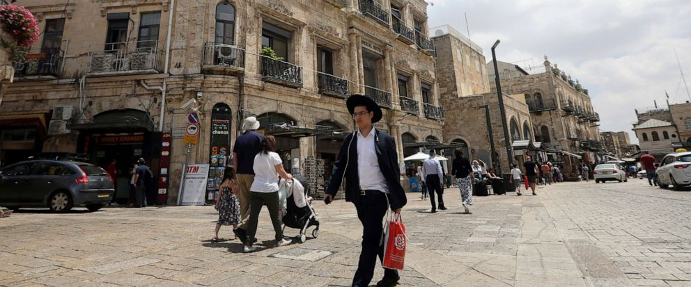 People walk past the Palestinian-run Imperial Hotel, that was part of a legal battle, in Jerusalems Old City, Thursday, June 13, 2019. Israels Supreme Court has ruled against the Greek Orthodox Church in a long-running legal battle over the sale of
