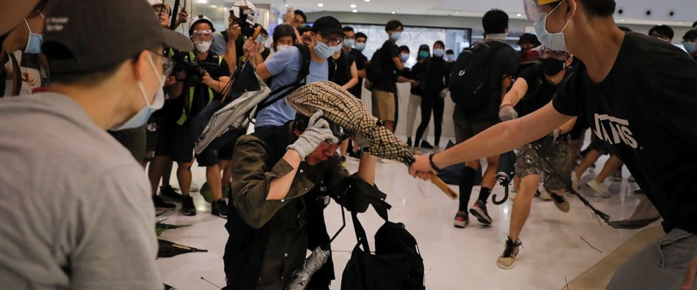 A policeman is attacked by protesters inside a mall in Sha Tin District in Hong Kong, Sunday, July 14, 2019. Police in Hong Kong have fought with protesters as they broke up a demonstration by thousands of people demanding the resignation of the Chin