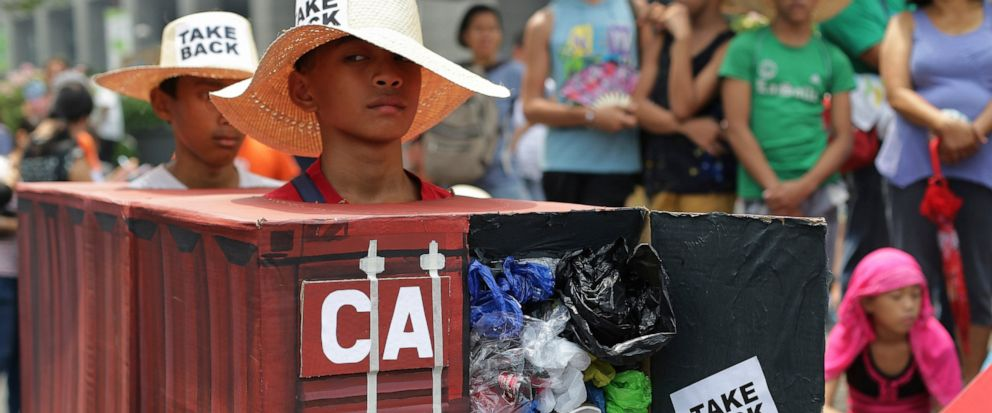 FILE - In this May 7, 2015, file photo, Filipino environmental activists wear a mock container vans filled with garbage to symbolize the 50 containers of waste that were shipped from Canada to the Philippines two years ago, as they hold a protest out