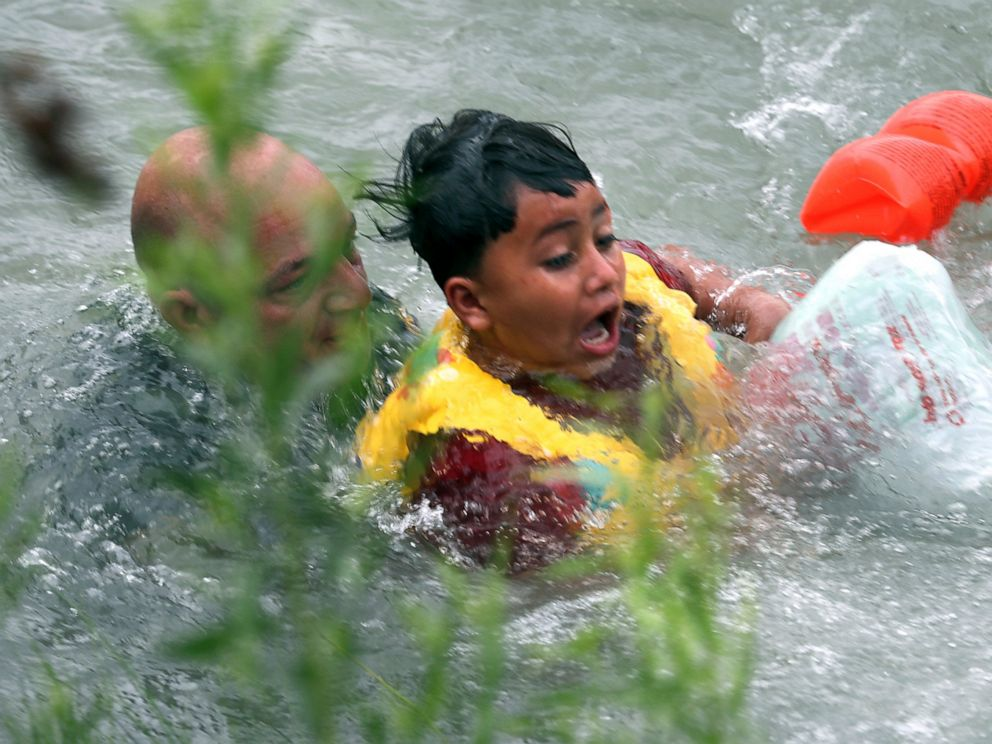 In this Friday, May 10, 2019 photo, Border Patrol Agent Brady Waikel rescues a 7-year-old boy from Honduras after he fell out of a makeshift raft and lost hold of his mother as Border Patrol agents respond to rafts crossing the Rio Grande River near