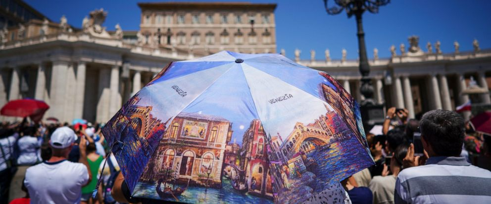 People shelter from the sun under a souvenir umbrella from Venice during the noon Angelus prayer recited by Pope Francis at the window of his studio overlooking St.Peters Square, at the Vatican, Sunday, July 14, 2019. (AP Photo/Andrew Medichini)