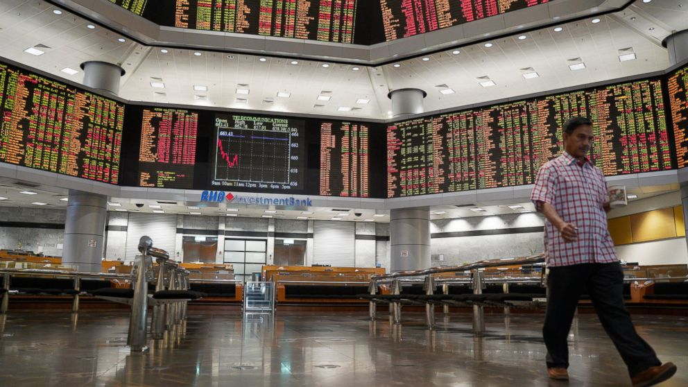 An investor walks in front of private stock trading boards at a private stock market gallery in Kuala Lumpur, Malaysia, Friday, Feb. 8, 2019. Asian markets tumbled on Friday after U.S. President Donald Trump said he doesn't plan to meet Chinese leader Xi Jinping before a tariffs ceasefire ends in March. (AP Photo/Yam G-Jun)