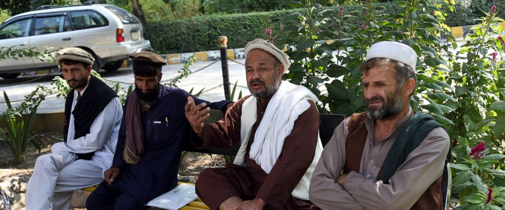 In this Tuesday, Oct. 1, 2019, photo, Aziz Rahman, second, right, a village elder, who had contracted the farmers to harvest the pine nuts, speaks during an interview to the Associated Press in Jalalabad city east of Kabul, Afghanistan, Anger is moun