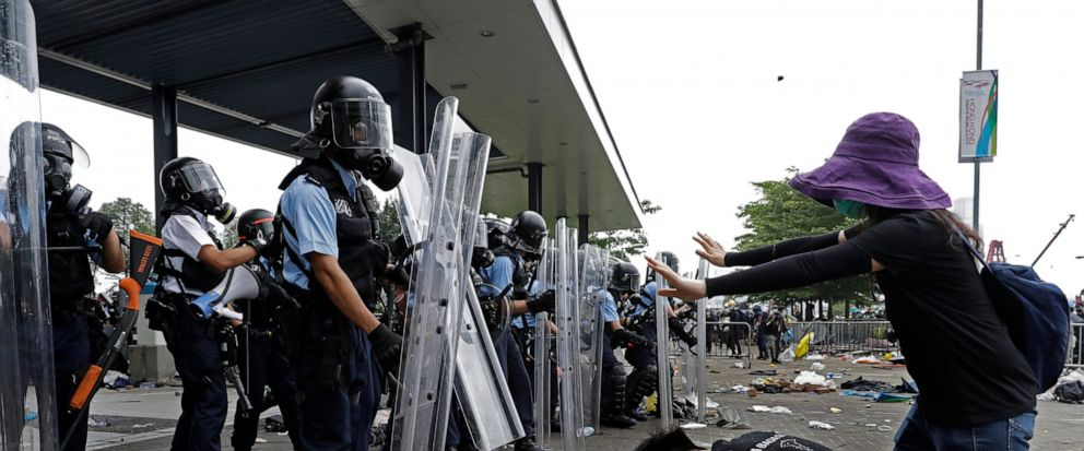 FILE - In this file photo taken Wednesday, June 12, 2019, a protester bows to riot police after they fire tear gas towards protesters outside the Legislative Council in Hong Kong. Hong Kong police have resorted to harsher-than-usual tactics to suppre