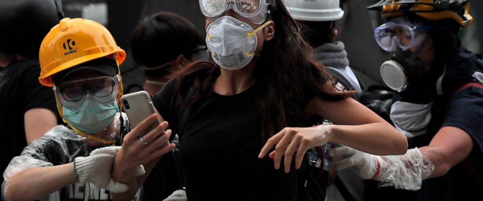 In this photo taken on Wednesday, June 12, 2019, protesters flee after police fired tear gas during a massive demonstration outside the Legislative Council in Hong Kong. Young Hong Kong residents protesting a proposed extradition law that would allow